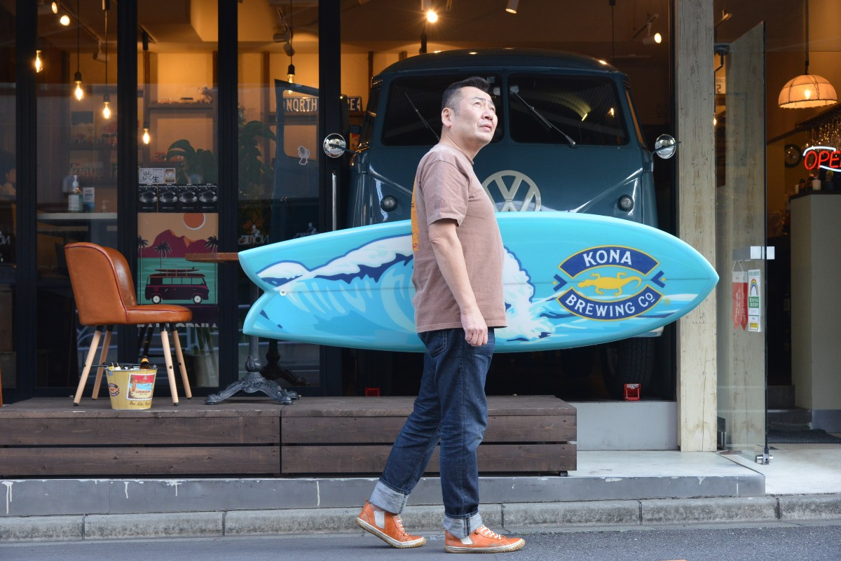 サーフボードを持って店の前を歩く店主・寺尾豊