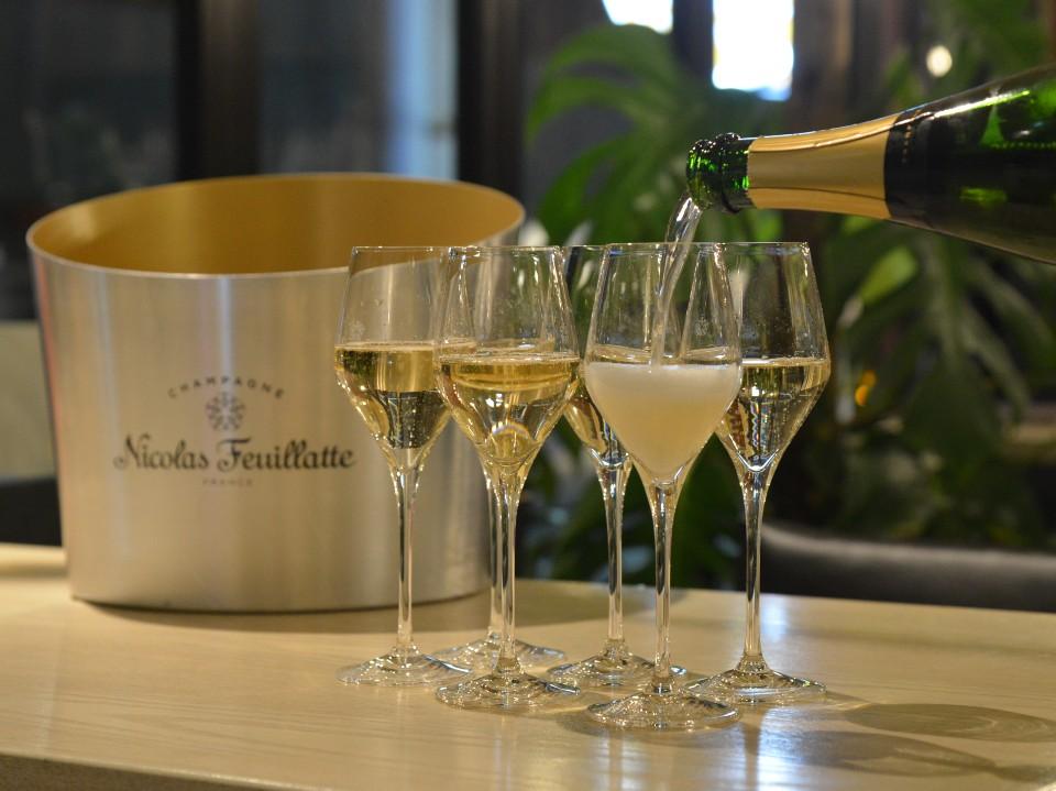 並んだシャンパン・グラスに注がれるシャンパン