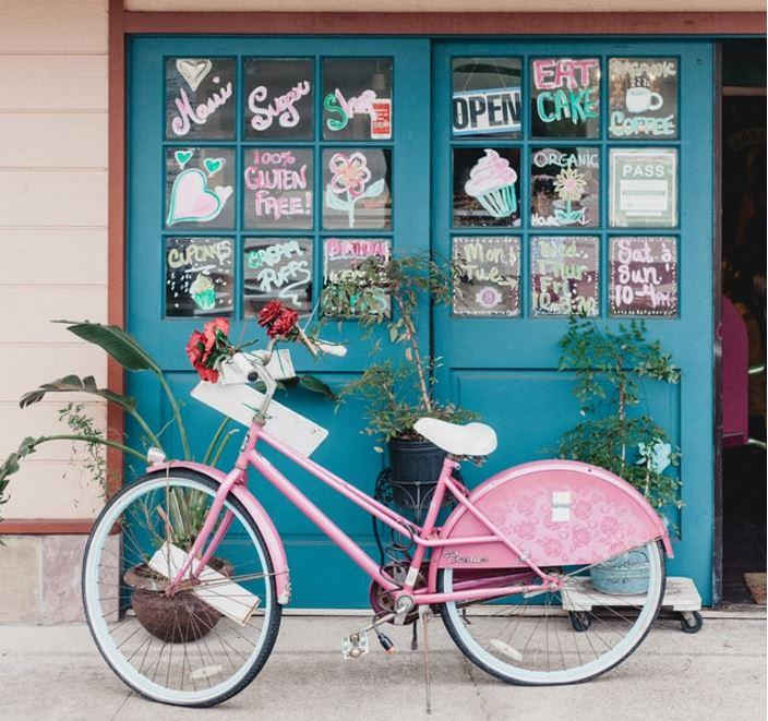 さまざまな言葉が書かれたウィンドウの前に停めたピンクの自転車