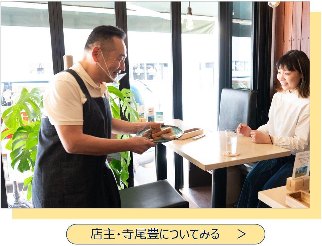 客席に料理を運ぶ店主・寺尾
