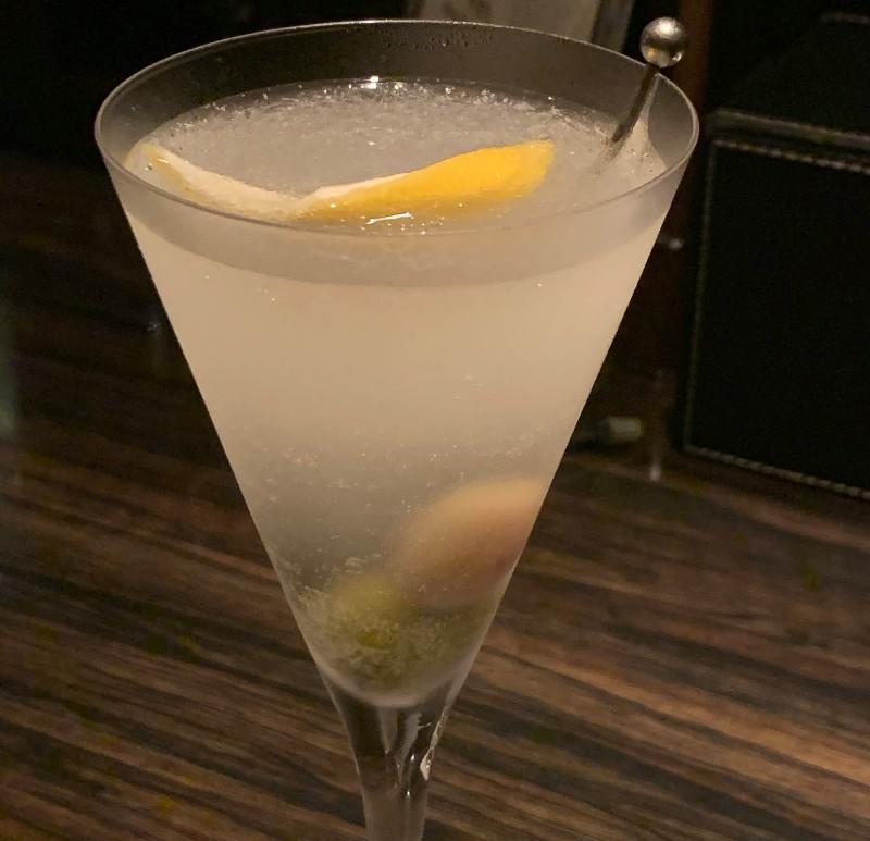 バーカウンターのカクテル。グラスの中にはレモンとオリーブの実が。