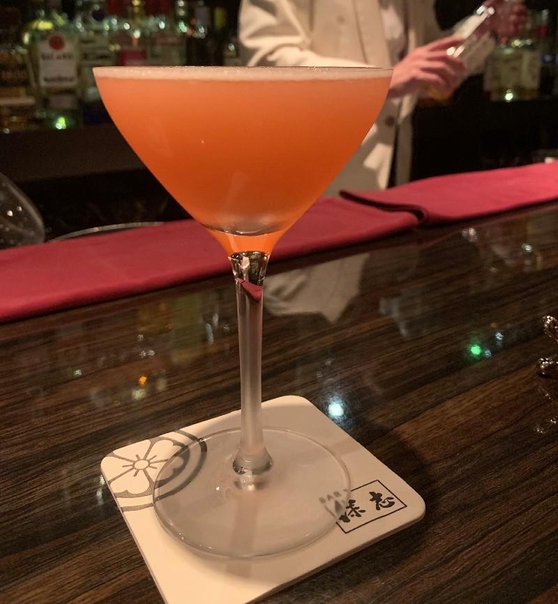 バーのカウンターに置かれたオレンジ色のカクテル。背後には白いスーツのバーテンダーが。