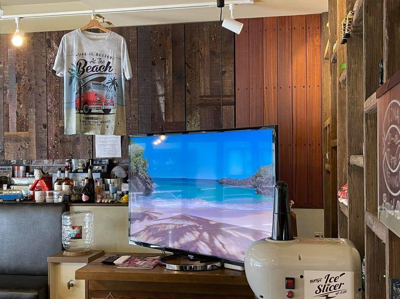 南の島のイメージビデオを大画面に流し、涼し気なカフェテラオの店内