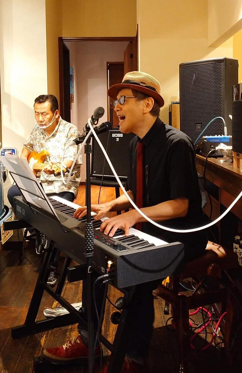 店内に電子ピアノを置いて弾き語りをする寺尾広さん